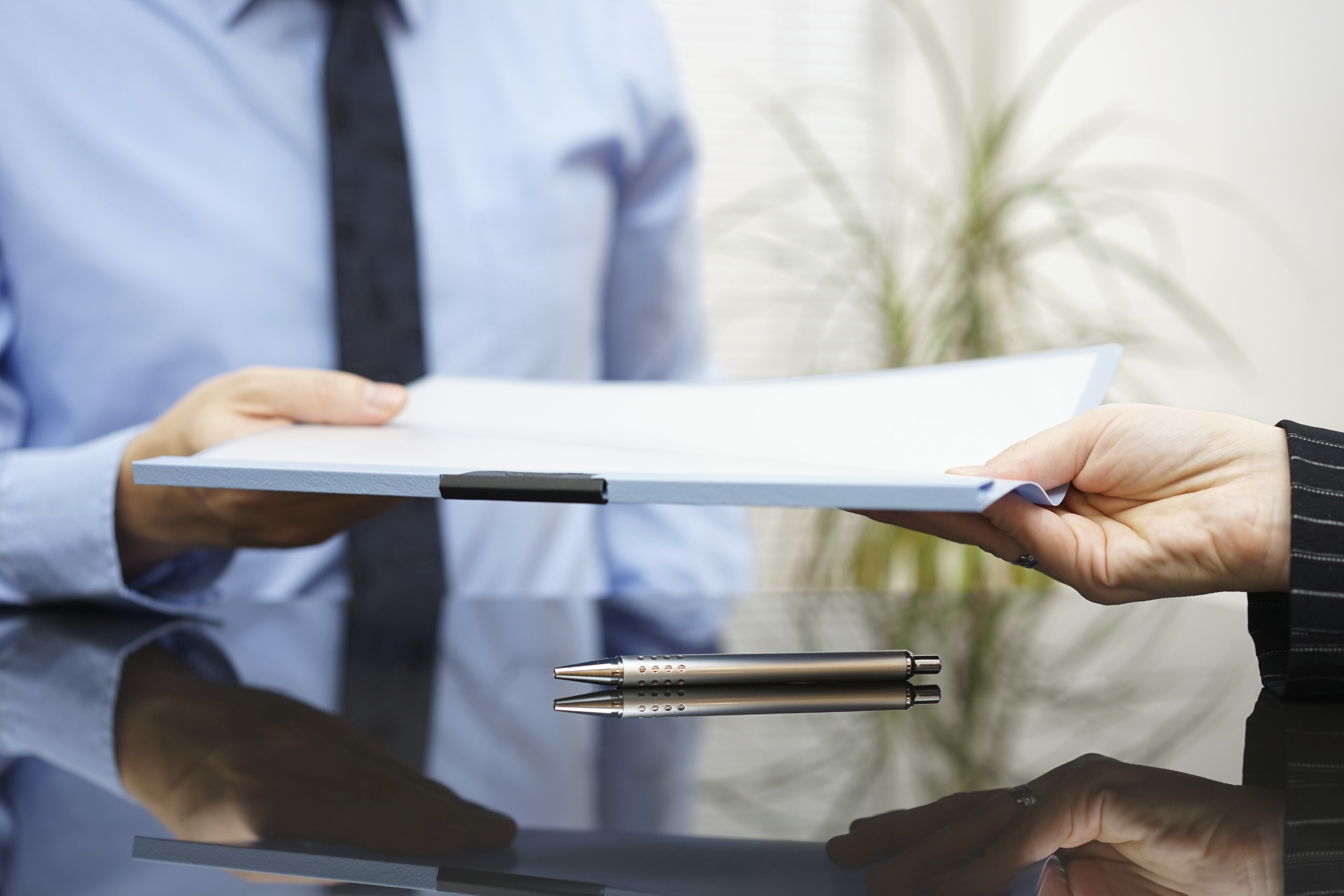 businessman is passing signed agreement to client after successf